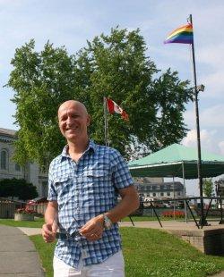 """Ethik-Professor Udo Schuklenk vor einer Regenbogenfahne in Kingston: """"Toronto selbst ist liberal, aber das Einzugsgebiet eher konservativ."""" - Quelle: Robert Niedermeier"""