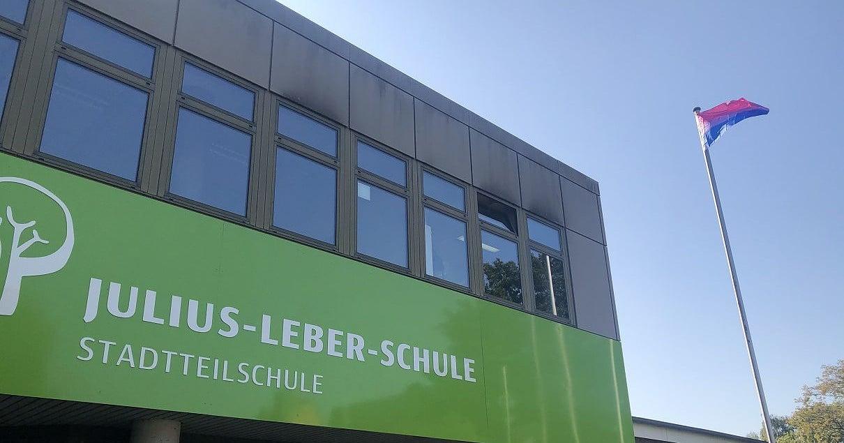 Die Bi-Flagge weht über einer Hamburger Schule